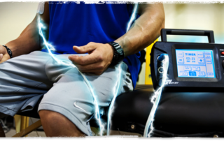 Muscular man sitting on bench wearing activewear with Evo Stimulator Device attached to biceps - device cords display an animated electric shock to demonstrate how it works