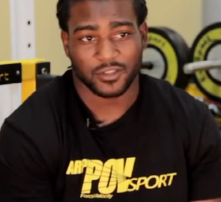 Tim Hightower wearing athletic shirt with gym weights and equipment in background